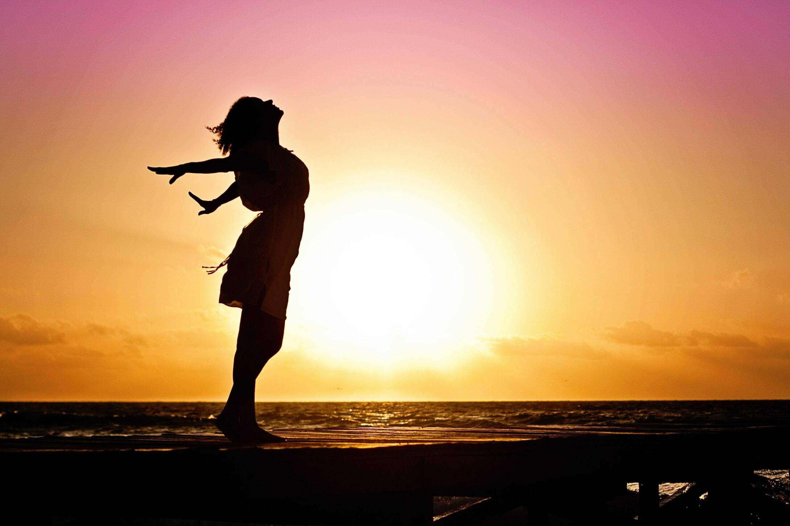silhouette of woman looking into the sunset