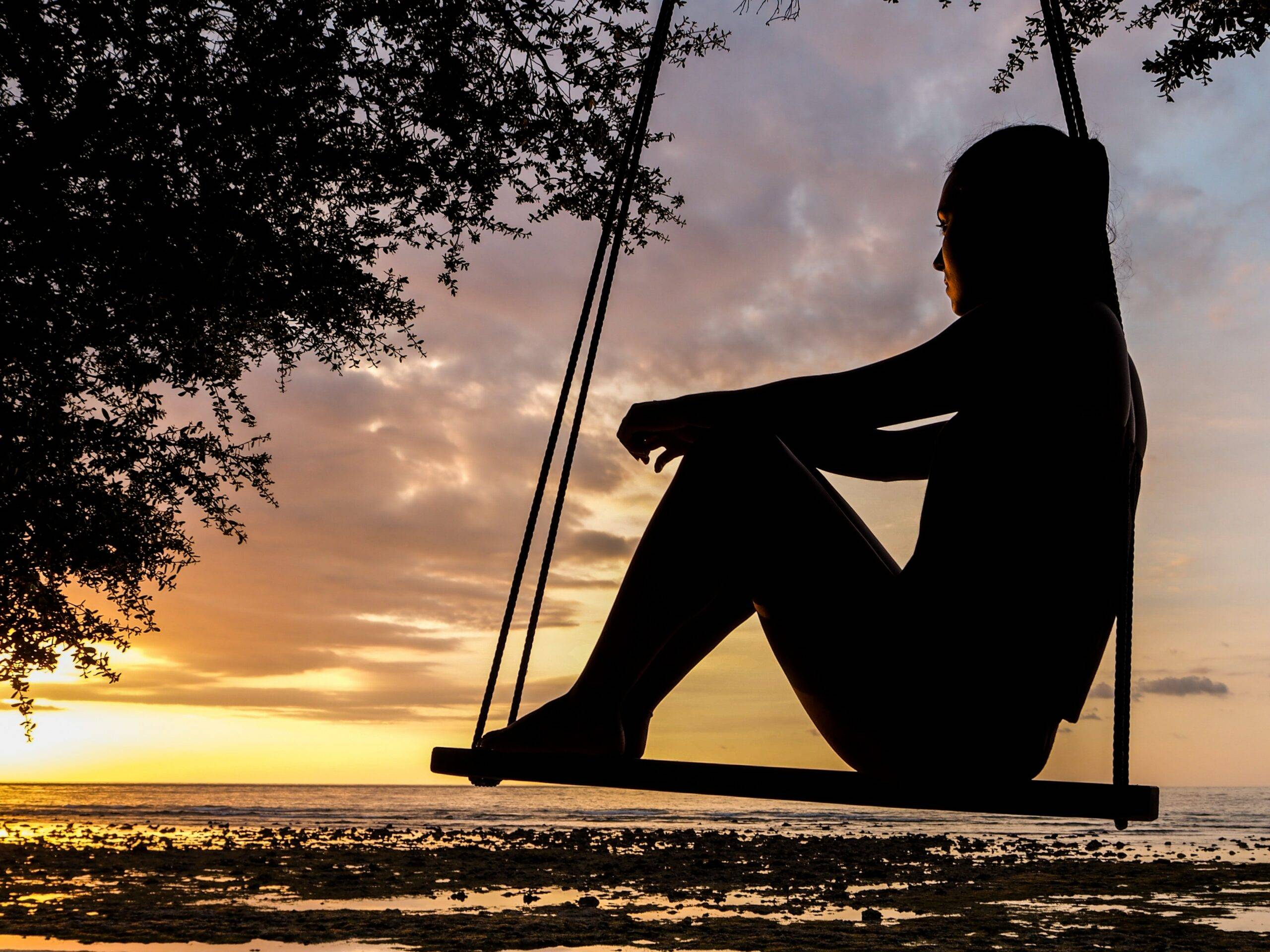 woman sitting on swing looking into the sunset